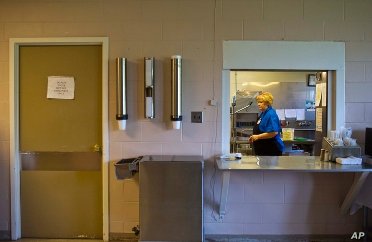 FILE- An employee cleans the hospital's cafeteria of Wedowee Hospital, in Wedowee, Alabama, July 30, 2015.