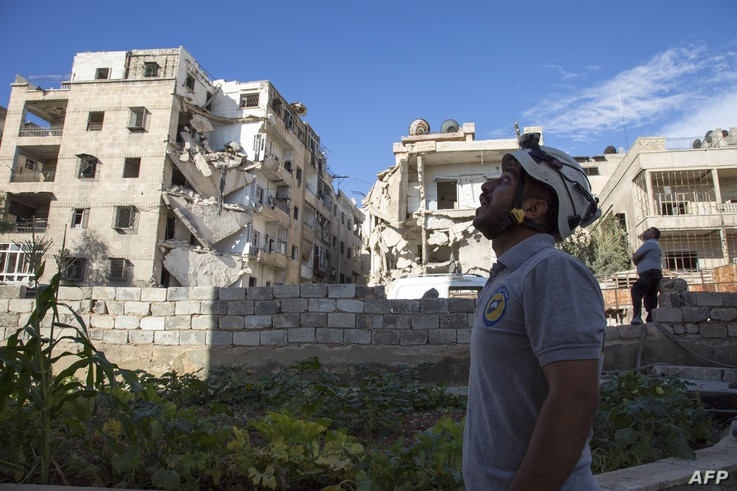 A rescuer looks towards the sky following an airstrike in the rebel-held Ansari district in the northern Syrian city of Aleppo, Sept. 23, 2016.
