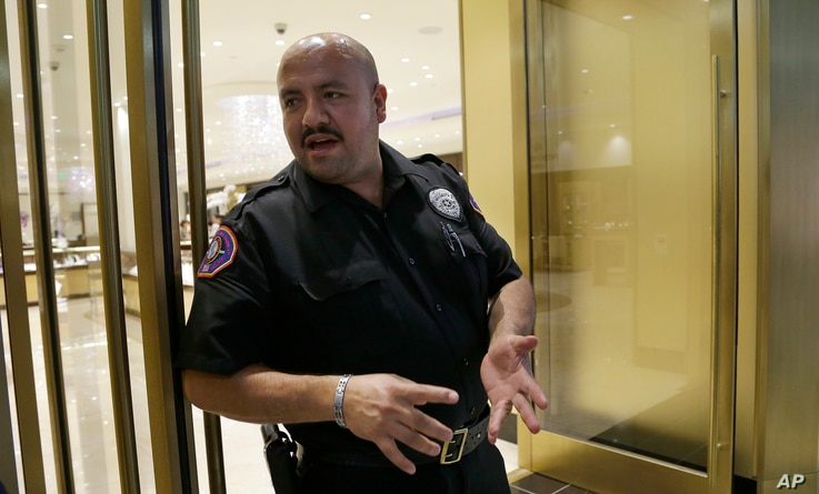 FILE - Security guard Eric Leon discusses automation while on duty at Westfield Valley Fair shopping center in San Jose, California, June 26, 2017.