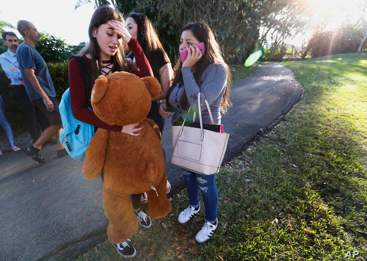 Students wait to be picked up after a shooting at Marjory Stoneman Douglas High School in Parkland, Fla., Feb. 14, 2018.