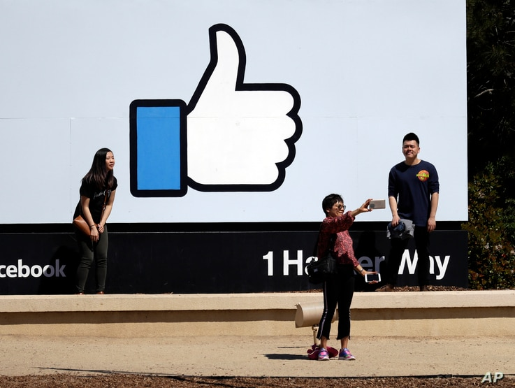 FILE - Visitors take photos in front of the Facebook logo at the company's headquarters, March 28, 2018, in Menlo Park, Calif.