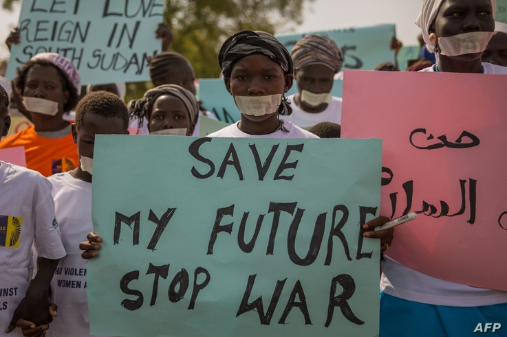 FILE - Women from more than forty South Sudanese womens organizations carry placards as march through Juba to express the frustration and suffering that women and children have endured after years of conflict, in Juba, South Sudan on Dec. 9, 2017.