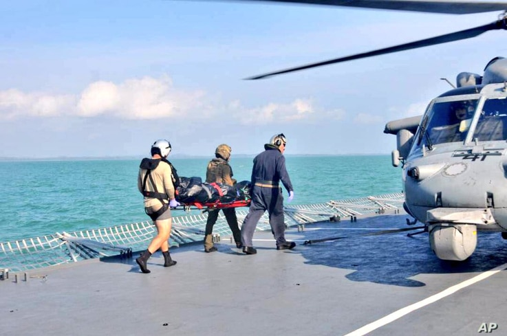 Royal Malaysian Navy personnel carry a body onto a U.S. Navy helicopter from USS America during a search and rescue operation for survivors of the USS John S. McCain
