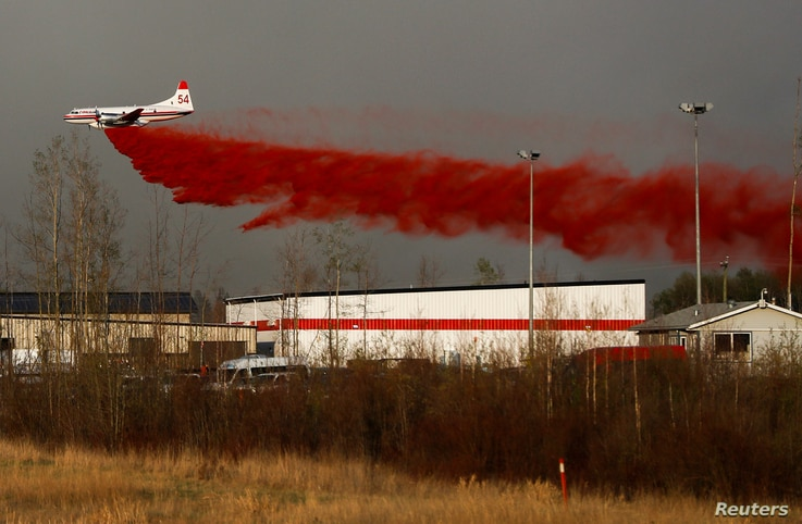 A plane flies low to dump fire retardant on wildfires near Fort McMurray, Alberta, Canada, May 6, 2016.