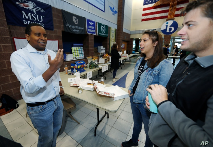Democratic candidate Joe Neguse for U.S. House District 2, left, greets canvassers as they head out to round up votes from Hinkley High School, Oct. 20, 2018, in Aurora, Colo.