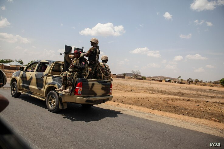 Nigerian soldiers drive along a road in northern Adamawa State, Nigeria on March 26, 2016.