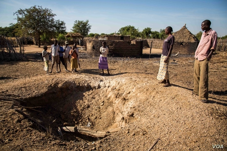 Omar Jajani and his family stand around a bomb crater made by an Antonov bomber. He says the bombing destroyed the whole compound where his home once was, everything is gone. (Adam Bailes/VOA News)