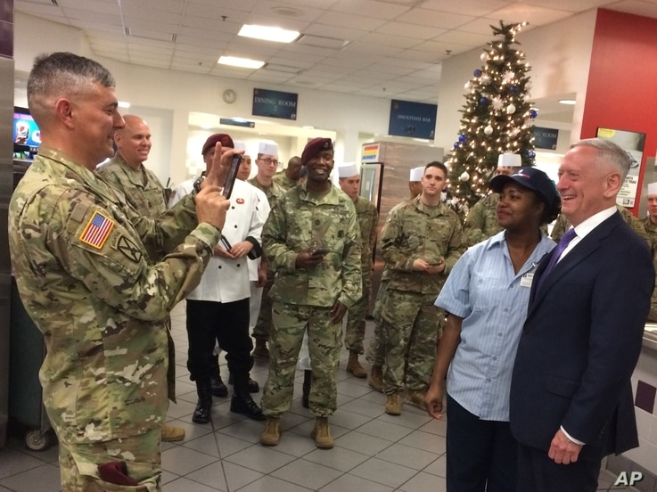 FILE - In this Dec. 22, 2017, file photo, Lt. Gen. Stephen Townsend takes a photo of Defense Secretary Jim Mattis and a dining facility worker at Fort Bragg, North Carolina.