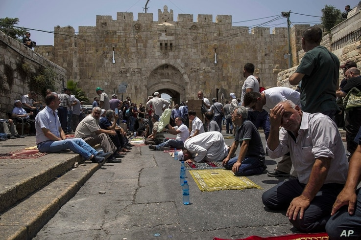 Palestinians pray outside the Lion's Gate in Jerusalem's Old City, July 21, 2017. Thousands of Muslims prayed  mats spread on cobble stone to protest the installation of metal detectors at the holy site.