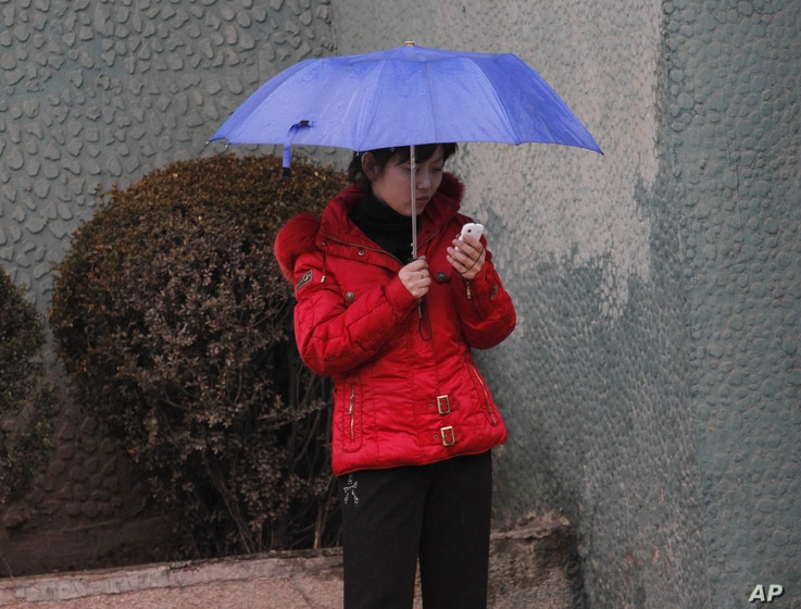 FILE - In this Friday March 16, 2012 file photo, North Korean woman uses a mobile phone on a sidewalk in Pyongyang, North Korea.