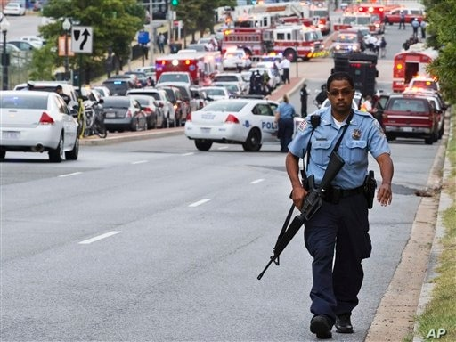 A Metropolitan Police Department officer walks near the Washington Navy Yard after at least one gunman launched an attack inside the naval installation, Sept. 16, 2013.