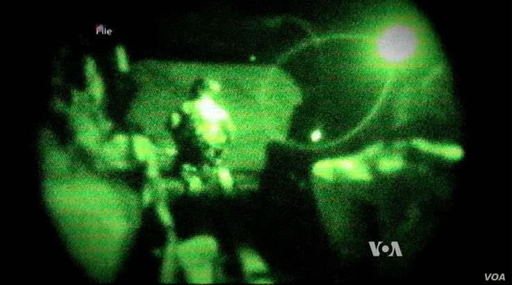 FILE - Screengrab of a video shot through night-vision lens shows U.S. servicemen conducting a mission in Iraq.