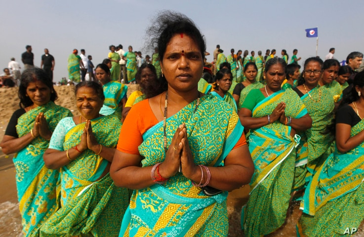 Indian women offer prayers on the Marina Beach at the Bay of Bengal to commemorate the 10th anniversary of the 2004 Tsunami in Chennai, India, Friday, Dec. 26, 2014.