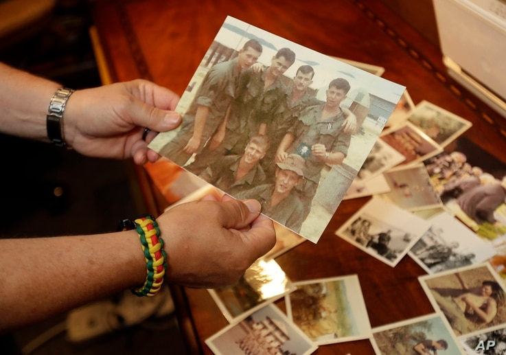 In a photo from June 9, 2017, in South Haven, Mich., former Army medic James McCloughan shows photos of himself and fellow soldiers in Vietnam.