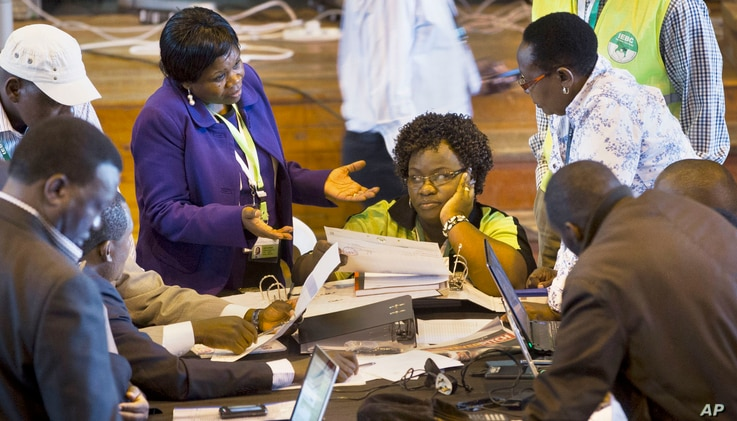 Official representatives of the various political parties and electoral workers discuss while reviewing newly received results, at the National Tallying Center in Nairobi, Kenya, March 6, 2013.
