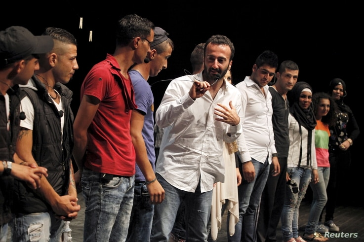 Director Lucien Bourjeily (C) talks alongside youth actors from Tripoli, North Lebanon, after their performance in a play he directed in Beirut, July 28, 2015.