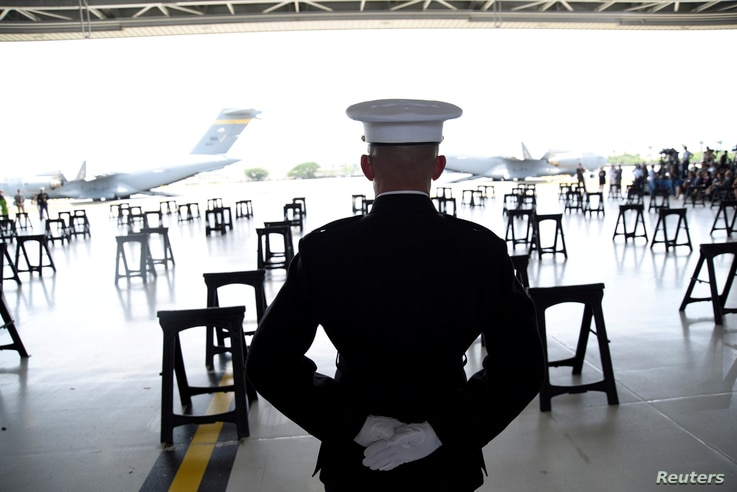 A U.S. Marine stands at attention as caskets containing the remains of American servicemen from the Korean War handed over by North Korea arrive at Joint Base Pearl Harbor-Hickam in Honolulu, Hawaii, U.S., Aug. 1, 2018.