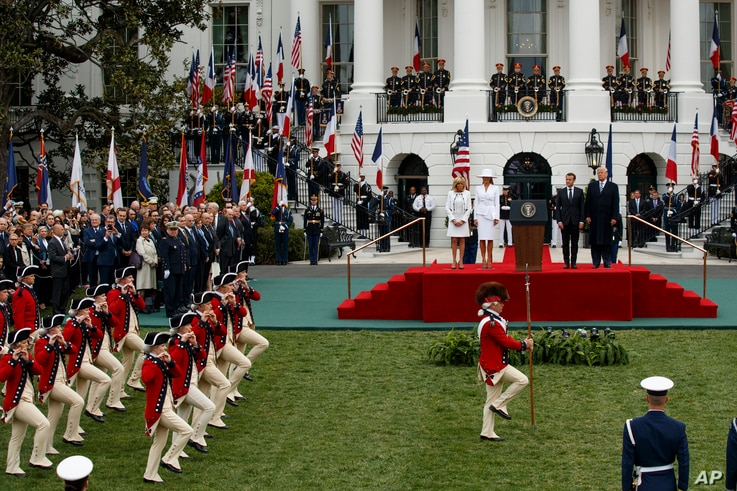 Brigitte Macron, first lady Melania Trump, French President Emmanuel Macron, and President Donald Trump look on during a State Arrival Ceremony on the South Lawn of the White House, April 24, 2018, in Washington.