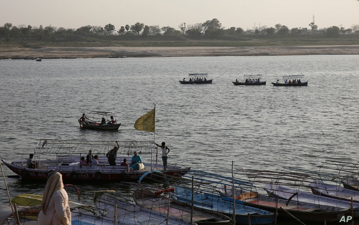 Indians ride on boats in the River Ganges, in Allahabad, March 21, 2017.