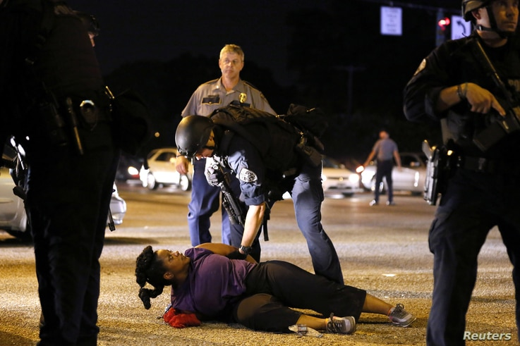 A woman protesting the shooting death of Alton Sterling is detained by law enforcement near the headquarters of the Baton Rouge Police Department in Baton Rouge, Louisiana, July 9, 2016.