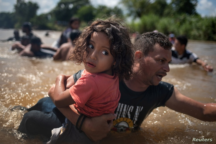 A man, part of a caravan of migrants from Central America en route to the United States, carries a girl through the Suchiate River into Mexico from Guatemala in Ciudad Hidalgo, Mexico, Oct. 29, 2018.