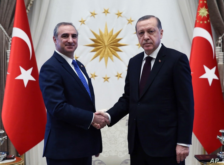 FILE - Turkey's President Recep Tayyip Erdogan, right, and Israeli Ambassador Eitan Naeh shake hands after Naeh presented his letter of credentials, in Ankara, Turkey, Dec. 5, 2016. Naeh arrived the previous week as the two countries seek to mend rel...