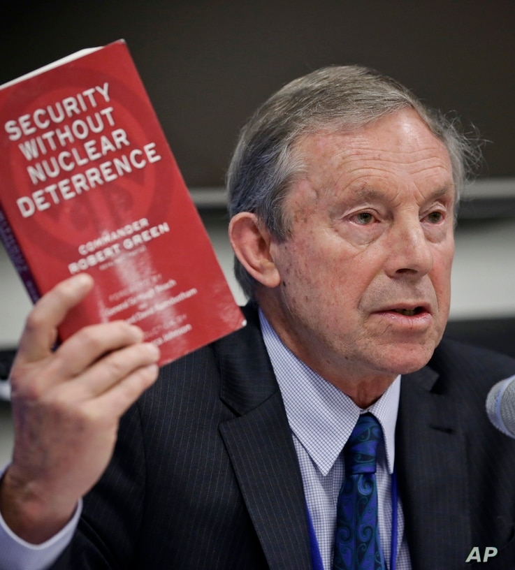 Former U.K. Naval commander Rob Green, co-director of Peace Foundation's Disarmament and Security Centre, displays his book as he speaks during a press briefing by experts on nuclear disarmament, discussing a new treaty to ban nuclear weapons, July 5...