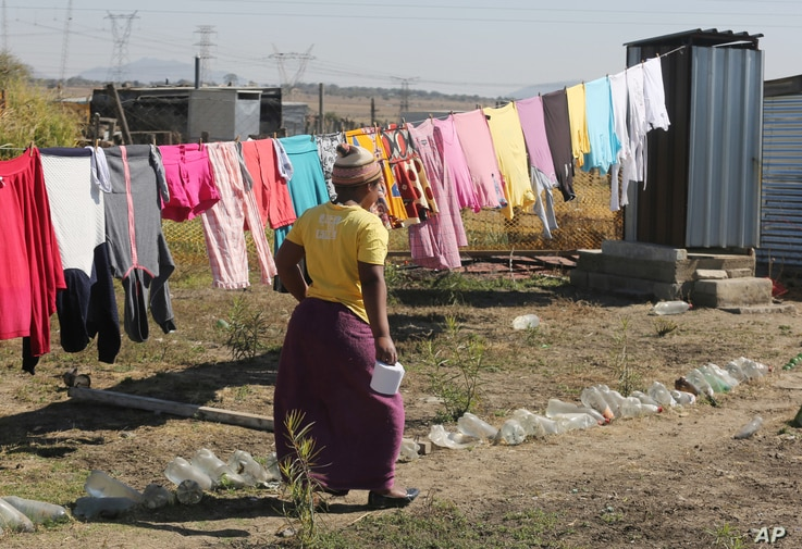 FILE - In this Aug. 12, 2016 photo, a woman heads to an outside pit latrine toilet where she shares a shack housing five people,  in Marikana, South Africa.