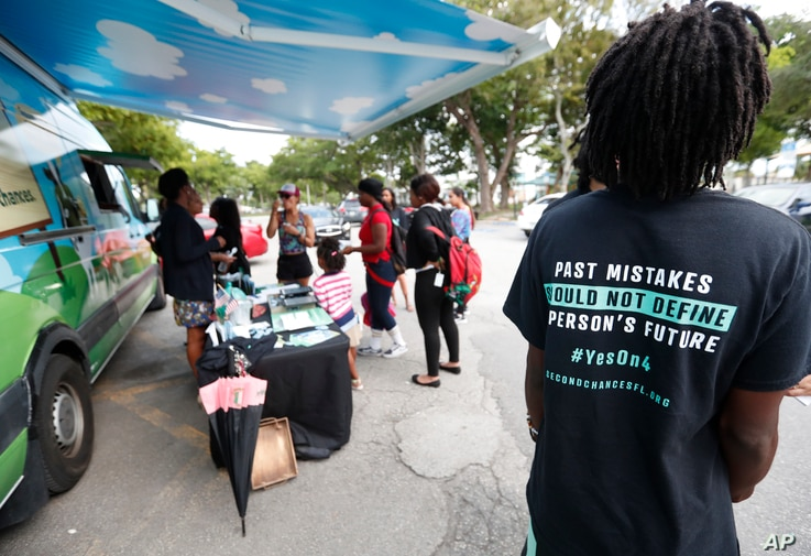 "In this, Monday, Oct. 22, 2018 photo, people gather around the Ben & Jerry's ""Yes on 4"" truck as they learn about Amendment 4 and eat free ice cream at Charles Hadley Park in Miami."