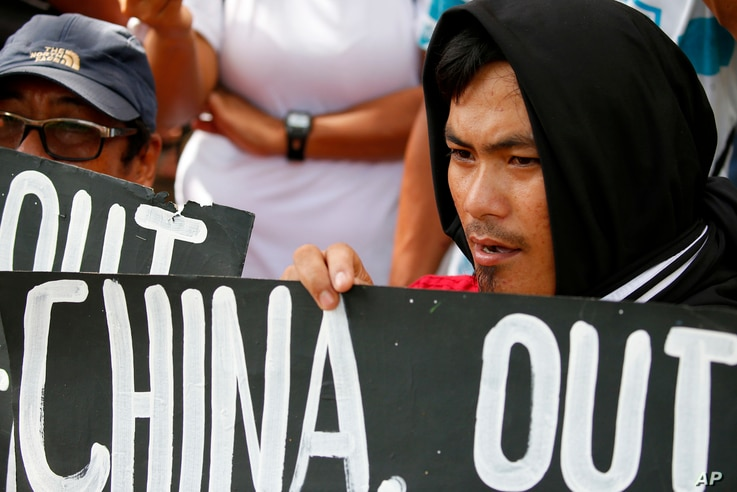 FILE - Protesters hold placards during a rally outside the Chinese Consulate in Manila to protest China's artificial island-building at the disputed islands, reefs and shoals off South China Sea.