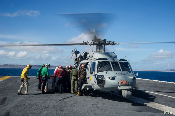 """Sailors aboard the U.S. Navy's forward-deployed aircraft carrier USS George Washington (CVN 73) load containers of water onto an MH-60S Seahawk from the """"Golden Falcons"""" of Helicopter Sea Combat Squadron (HSC) 12 in support of Operation Damayan, Nov...."""