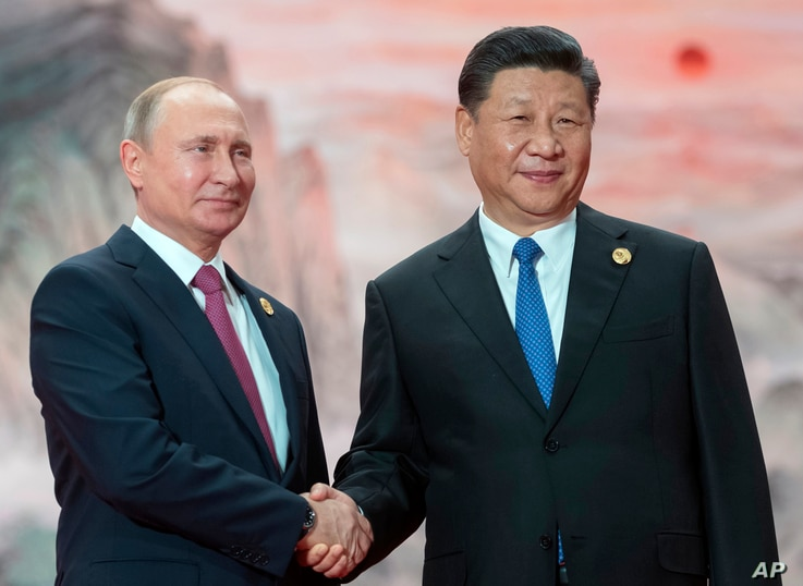 Chinese President Xi Jinping, right, and Russian President Vladimir Putin pose for a photo at the Shanghai Cooperation Organization (SCO) Summit in Qingdao in eastern China's Shandong Province, June 10, 2018.