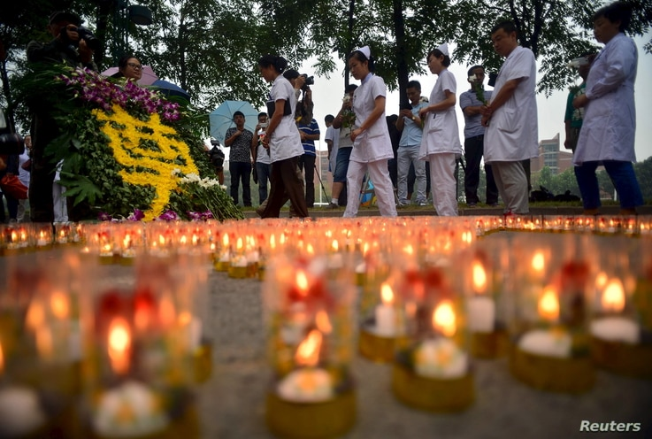 Medical workers, marking the seventh day since the Tianjin explosions, pay tribute to the people who died, in a ceremony at Binhai new district, Tianjin, China, Aug.18, 2015.