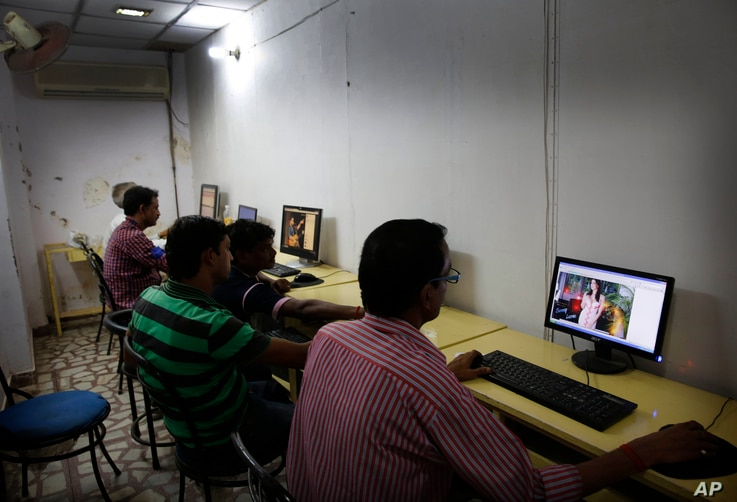 FILE - Indian youth use the internet at a cyber cafe in Allahabad, India.