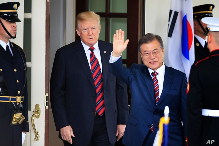 FILE - South Korean President Moon Jae-in waves as he is welcomed by U.S. President Donald Trump to the White House in Washington, May 22, 2018. South Korea said Friday that Moon will travel to the United States April 10-11 to meet with Trump for a s