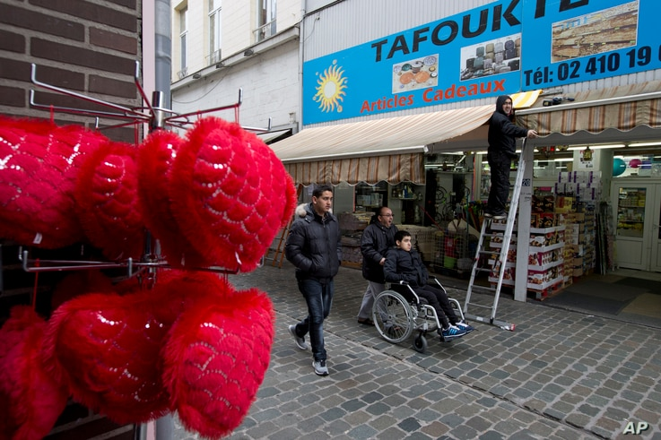 People pass a shop in the Molenbeek neighborhood of Brussels, March 19, 2016, where fugitive Salah Abdeslam was arrested after a four-month manhunt.