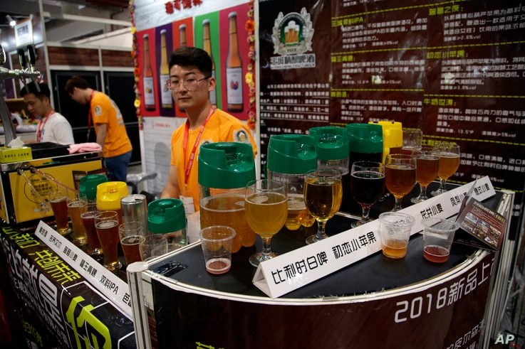 A vendor waits for visitors at a beer booth at the 2018 Craft Beer of China Exhibition in Shanghai, May 16, 2018.