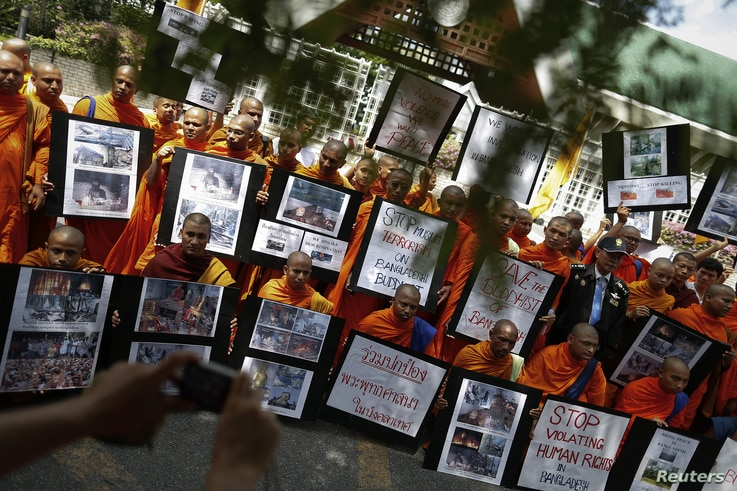 Buddhist monks hold banners and photographs as they protest in front of the U.N. office in Bangkok, Thailand, October 3, 2012.