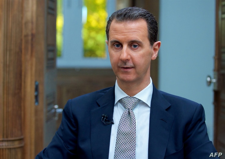 A handout picture released by the Syrian presidency's press office shows Syrian President Bashar al-Assad during an interview with AFP in the capital Damascus, on April 12, 2017.
