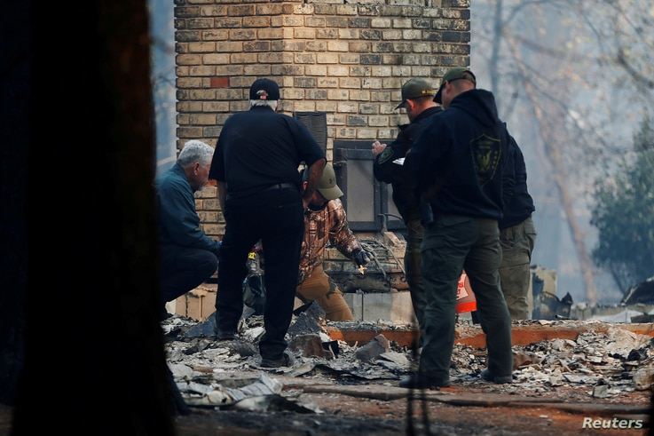 Yuba and Butte County Sheriff deputies retrieve remains of a deceased victim from a home during the Camp Fire in Paradise, California, U.S., Nov. 10, 2018.