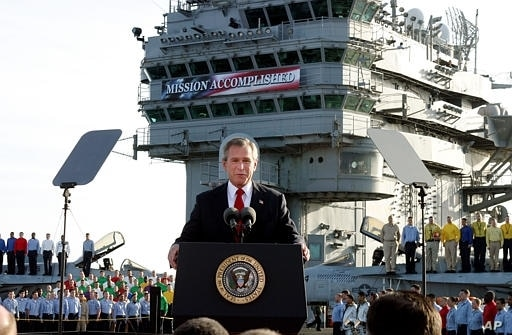 "Then President George Bush declares the war over in Iraq May 1, 2003. Behind him on board the carrier USS Abraham Lincoln is a banner reading: ""Mission Accomplished."""
