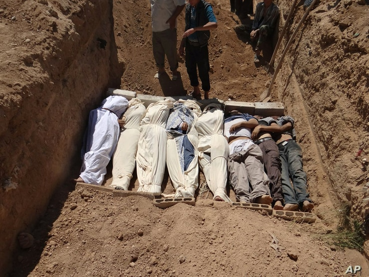 This image provided by Shaam News Network Aug. 22, 2013,  which has been authenticated based on its contents and other AP reporting, purports to show several bodies being buried in a suburb of Damascus, Syria during a funeral on Aug. 21, 2013.