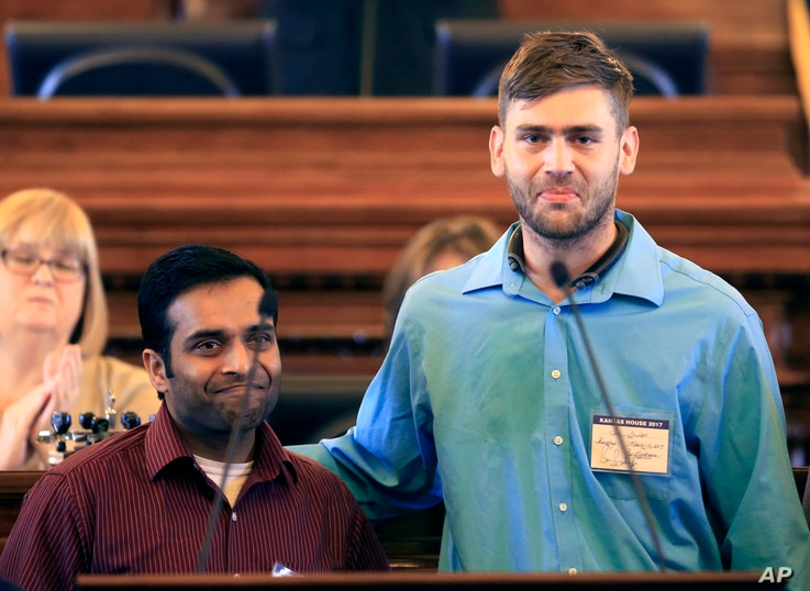 FILE - Alok Madasani (left) and Ian Grillot embrace after they were honored by the Kansas House of Representatives in Topeka, Kan. Adam Purinton was indicted by a federal grand jury, June 9, 2107, for a shooting in a suburban Kansas City bar. Sriniv...
