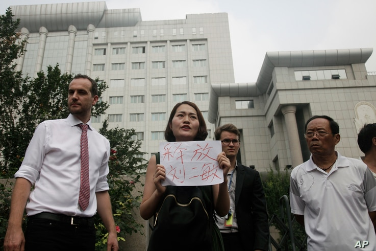"""Li Wenzu, center, wife of imprisoned lawyer Wang Quanzhang, holds a paper that reads """"Release Liu Ermin"""" as she and supporters of a prominent Chinese human rights lawyer and activists stage a protest outside the Tianjin No. 2 Intermediate People's Co"""