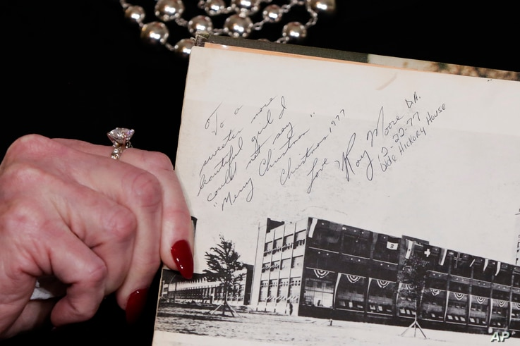 Beverly Young Nelson the latest accuser of Alabama Republican Roy Moore, shows her high school yearbook signed by Moore, at a news conference, in New York, Nov. 13, 2017.