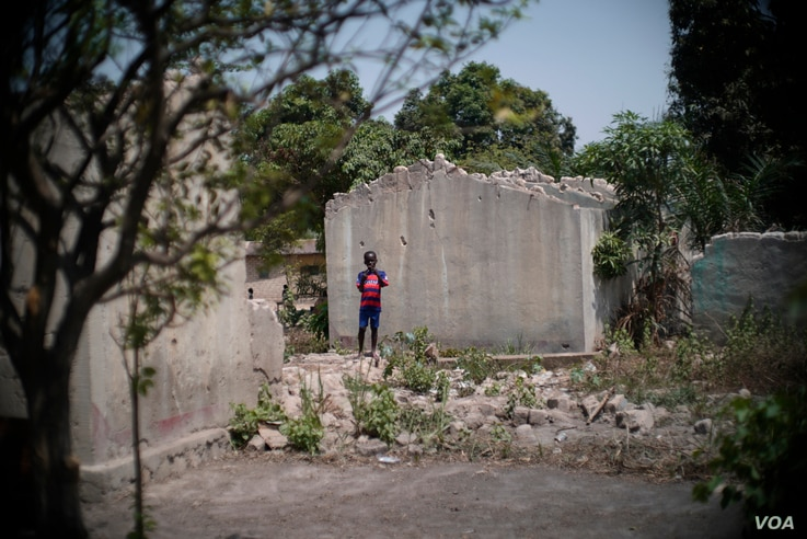 A young boy stands next to the shell of a home that was destroyed in the PK5 neighborhood of Bangui, February 2017. (Z. Baddorf/VOA)