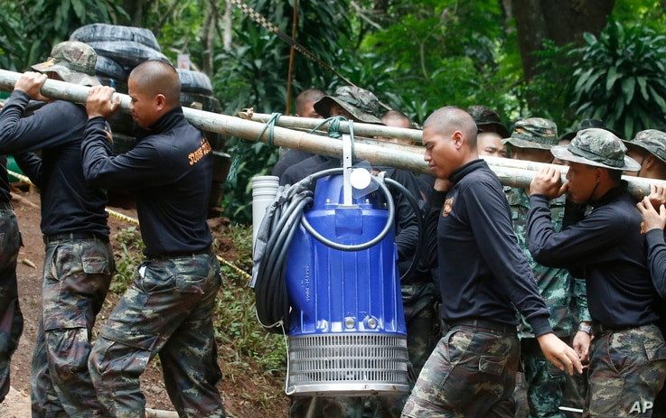 Soldiers carry a pump to help drain the rising floodwater in a cave where 12 boys and their soccer coach have been trapped since June 23, in Mae Sai, Chiang Rai province, in northern Thailand, July 6, 2018.