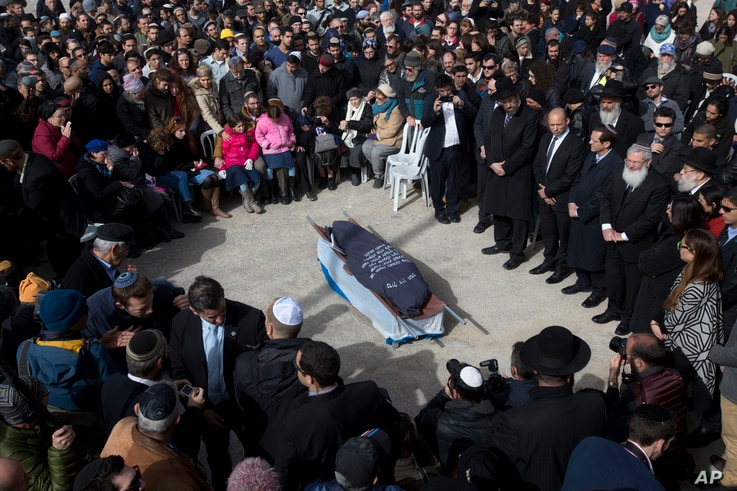Family and friends of Israeli Dafna Meir attend her funeral in a cemetery in Jerusalem Monday, Jan. 18, 2016. A Palestinian broke into a West Bank settlement home and fatally stabbed an Israeli woman before fleeing Sunday, touching off a massive nigh...