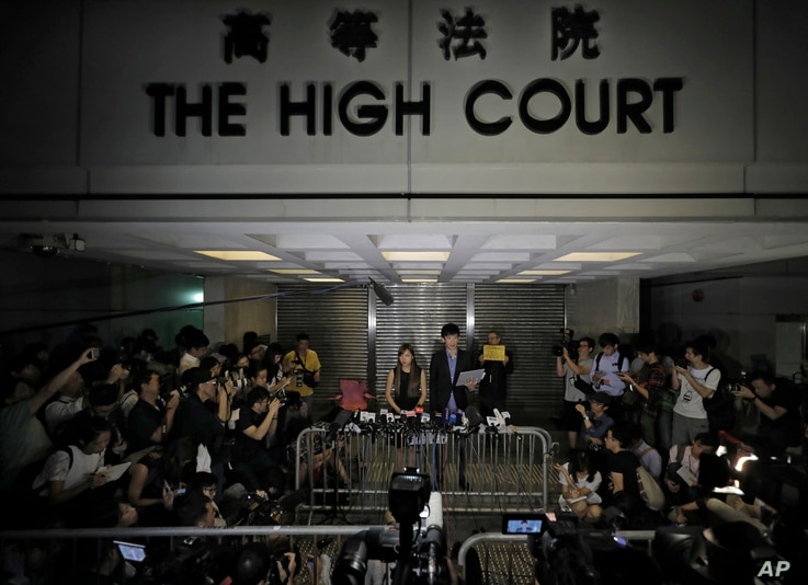 Newly elected Hong Kong lawmakers Yau Wai-ching (centre left) and Sixtus Leung talk to journalists during a press conference outside the high court in Hong Kong, Nov. 15, 2016. A Hong Kong High Court judge ruled that Sixtus Leung and Yau of the Youn...