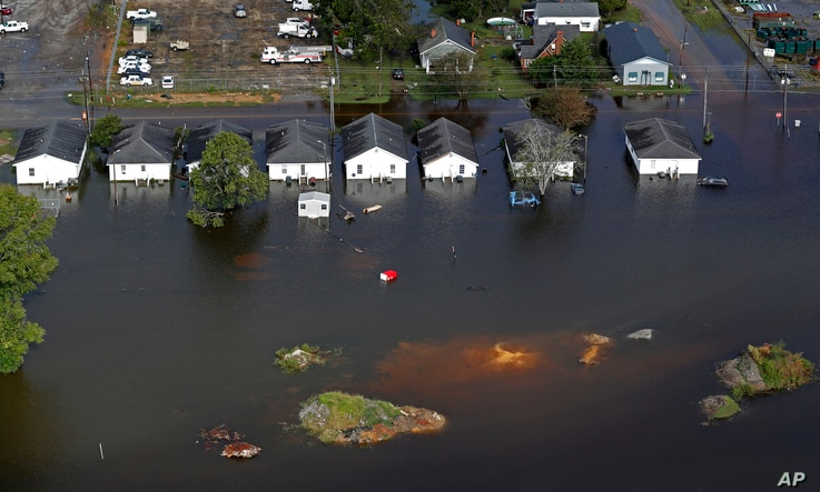 FILE - In this Sept. 17, 2018 file photo, floodwaters from Hurricane Florence surrounds homes in Dillon, South Carolina.